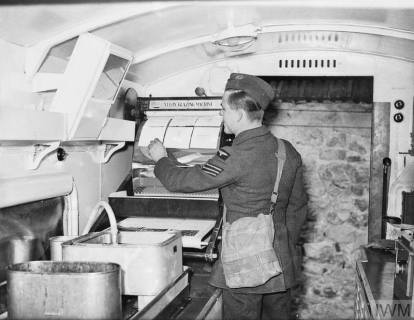 The sergeant in charge of the Photography Section at Bétheniville, France, glazing aerial reconnaissance prints inside a Mobile Darkrooms tender.